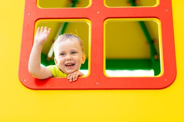 Ragazzino felice che gioca nel parco giochi, ragazzo che guarda fuori dalla finestra