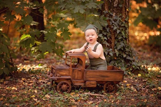 Ragazzino felice che si siede nell'automobile del giocattolo dei bambini di legno all'aperto in estate