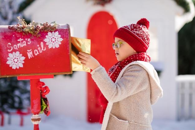 Ragazzino felice con cappello rosso e occhiali verdi inviando la sua lettera a babbo natale, tempo di natale