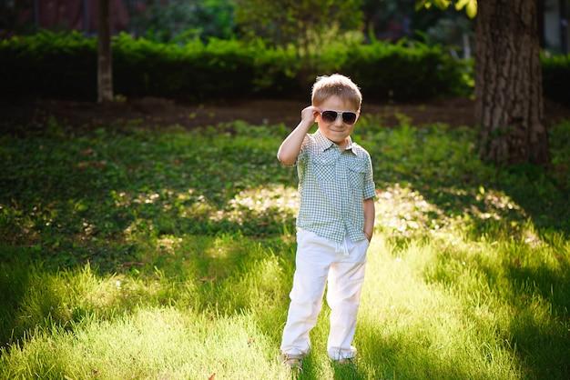 Ragazzino felice con gli occhiali da sole nel giardino.