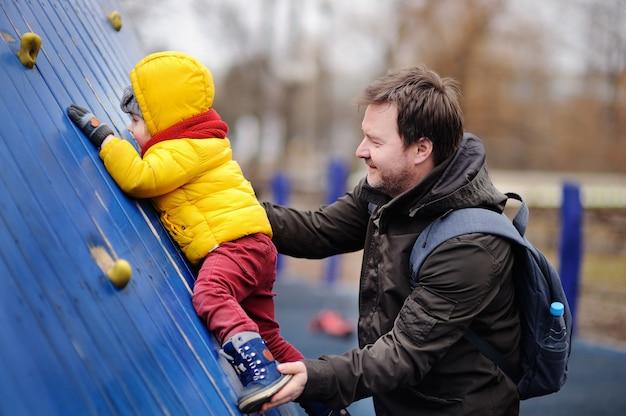 Ragazzino felice con suo padre divertendosi nel parco giochi all'aperto. primavera e autunno tempo libero attivo per i bambini.
