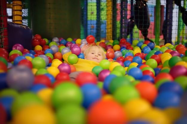 Ragazzino felice divertendosi nel pozzo della palla con le palle variopinte