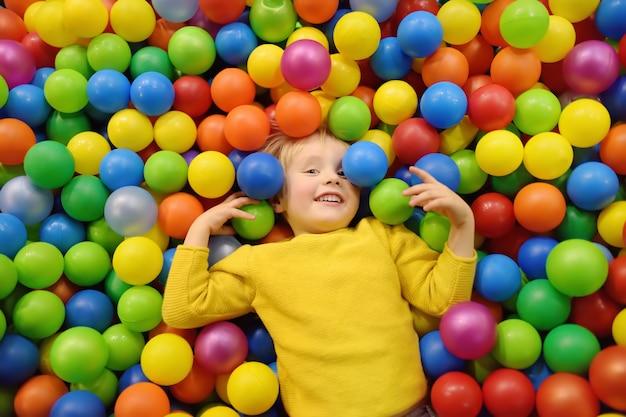 Ragazzino felice divertendosi nel pozzo della sfera con le sfere variopinte.