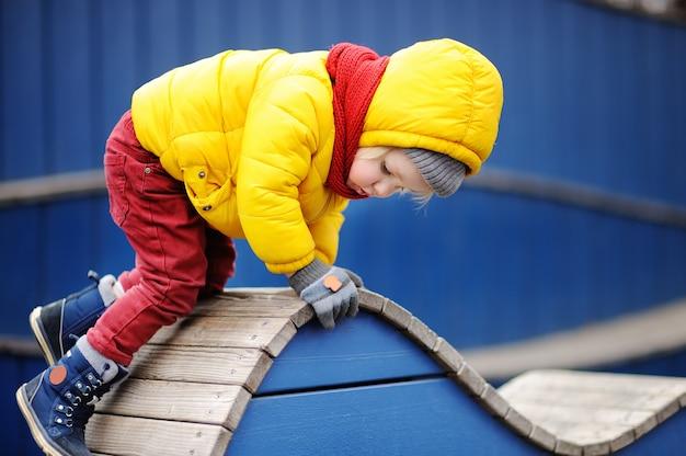Ragazzino felice divertendosi sul campo da giuoco all'aperto primavera e autunno tempo libero attivo per i bambini.