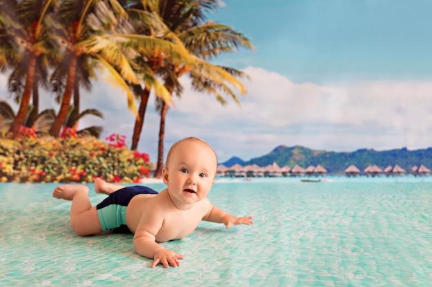Ragazzino felice nuota nel mare vicino alla spiaggia di sabbia con palme e bungalow