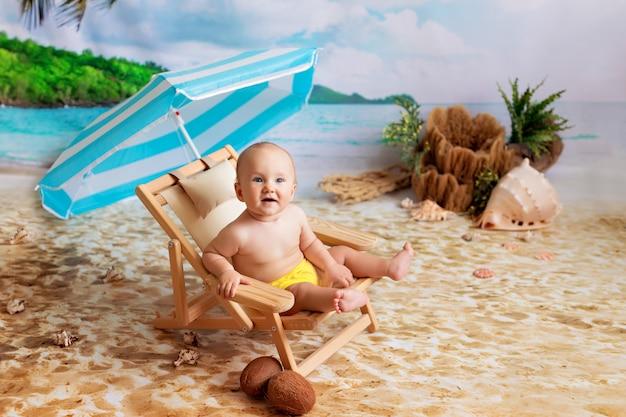 Ragazzino felice, si trova su una sedia a sdraio in legno, prende il sole sulla spiaggia di sabbia con palme in riva al mare