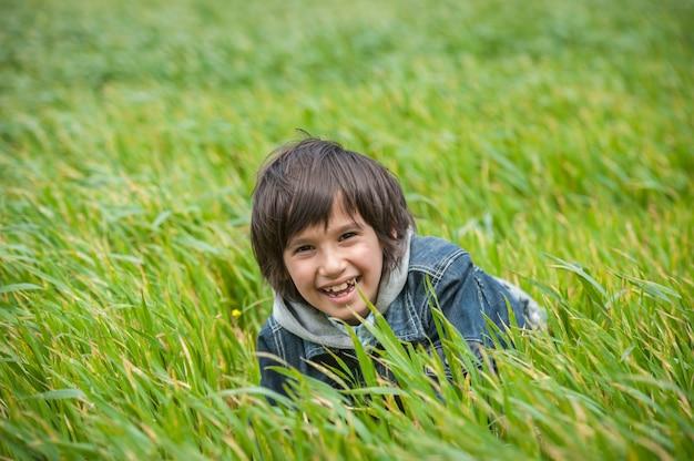 Ragazzino felice sul bello prato verde dell'erba gialla