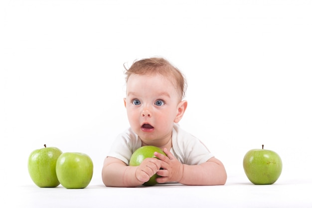 Ragazzino felice sveglio in camicia bianca tenere mela verde