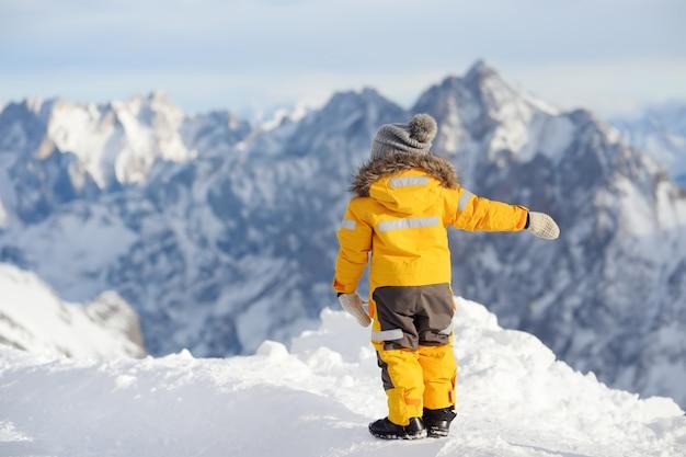 Ragazzino godendo la vista delle montagne alp inverno.