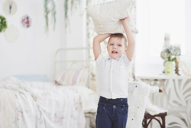 Ragazzino in camicia bianca con cuscino. battaglia di cuscini