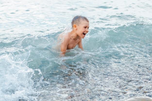 Ragazzino in costume da bagno che spruzza le gambe nel mare