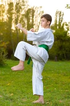 Ragazzino in kimono bianco durante l'allenamento esercizi di karate in estate all'aperto