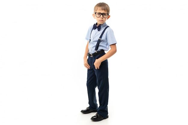 Ragazzino in occhiali neri con occhiali trasparenti, camicia blu, cavalletti