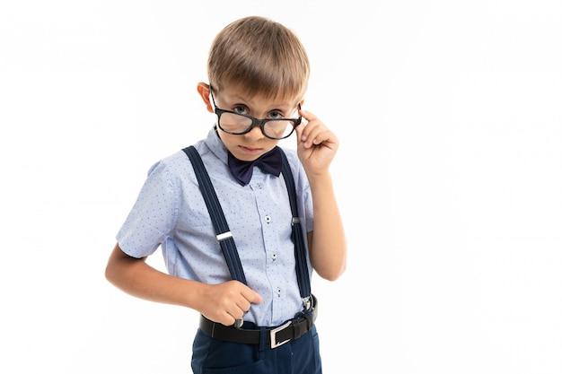 Ragazzino in occhiali neri con occhiali trasparenti, camicia blu, pull-up guarda la telecamera