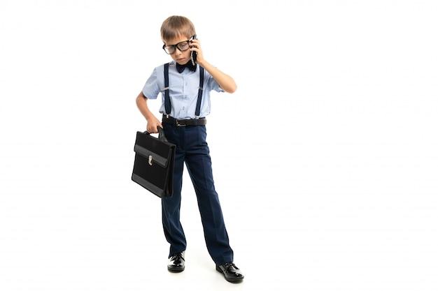 Ragazzino in occhiali neri con occhiali trasparenti, camicia blu, pull-up, pantaloni blu, custodia nera parla al telefono