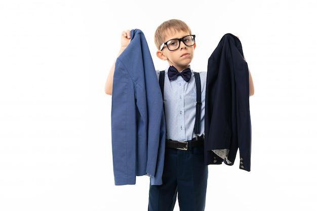 Ragazzino in occhiali neri con occhiali trasparenti, camicia blu, pull-up sceglie tra giacca nera e blu