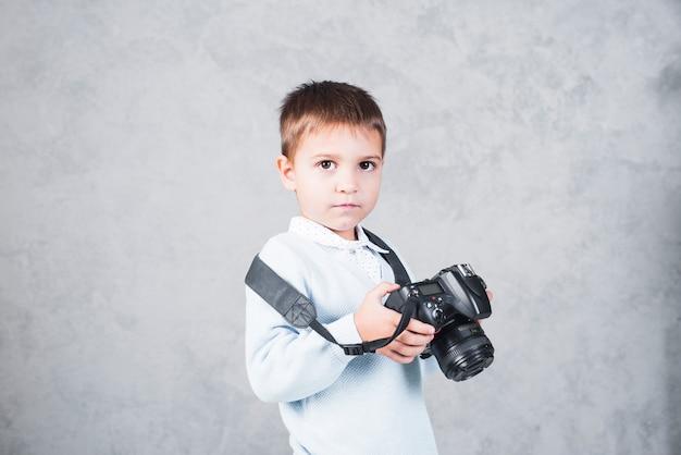 Ragazzino in piedi con la macchina fotografica