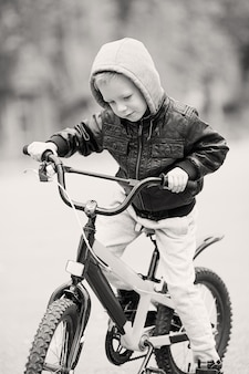 Ragazzino in sella a una bicicletta all'aperto