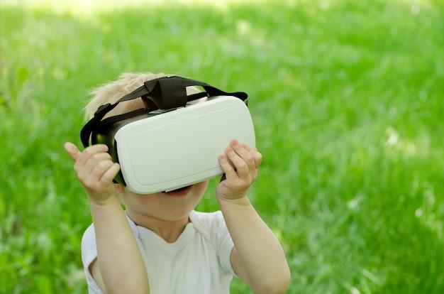 Ragazzino in un casco di realtà virtuale sulla superficie di erba verde