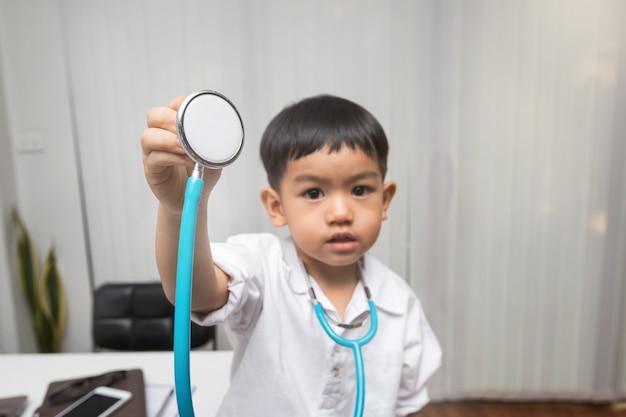 Ragazzino in uniforme dell'erba medica che tiene uno stetoscopio