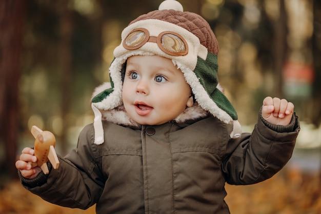 Ragazzino nel cappuccio pilota che gioca con l'aereo del giocattolo nel parco. autunno. concetto