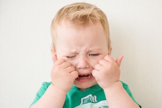 Ragazzino piange chiudendo il viso con le mani