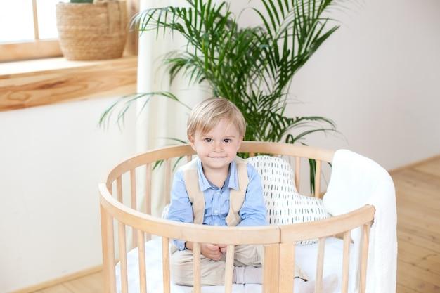 Ragazzino. ritratto di un ragazzo felice che gioca in una culla. il ragazzo si siede da solo in una culla nella scuola materna. un bambino solitario resta nella culla. bambino waif. il bambino a letto sorride. cameretta interna per bambini.