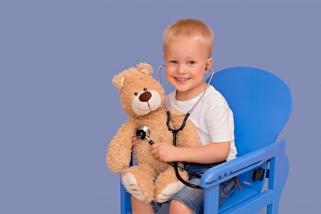 Ragazzino sorridente che gioca un medico e che ascolta un orsacchiotto con uno stetoscopio