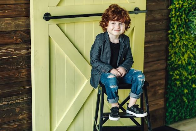 Ragazzino sorridente in jeans strappati che si siedono sulla scala e sullo sguardo rilassato