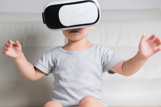 Ragazzino sul divano con l'auricolare virtuale
