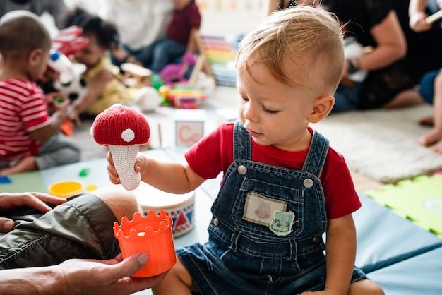 Ragazzino sveglio che gioca con i giocattoli al centro di apprendimento