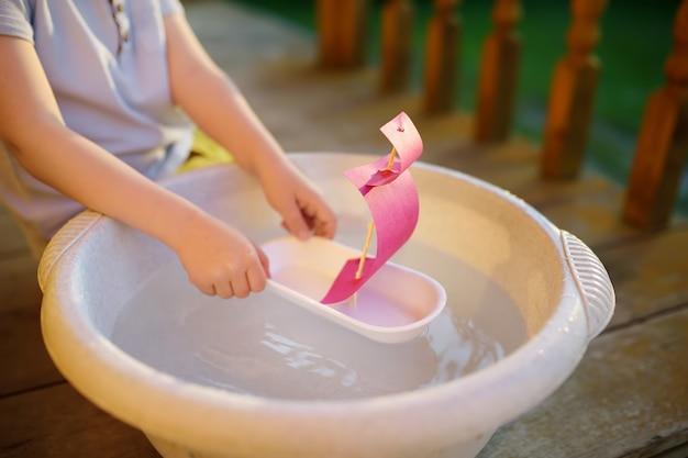Ragazzino sveglio che gioca con la nave fatta in casa nel bacino d'acqua sotto il portico di casa. i bambini giocano.