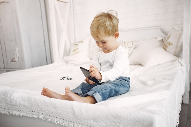 Ragazzino sveglio che gioca con un computer portatile su un letto