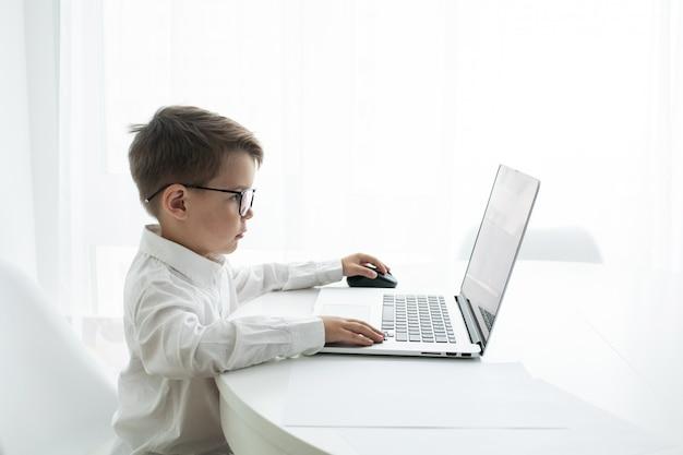 Ragazzino sveglio che per mezzo del computer portatile mentre facendo i compiti contro il bianco