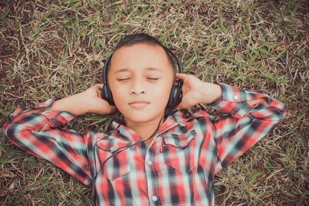 Ragazzino sveglio che si trova sull'erba con la cuffia per l'ascolto nel parco, il suo viso sembra felice con il sole. il soggetto è sfocato.