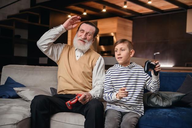 Ragazzino sveglio con il nonno che si siede sul sofà e che gioca video gioco con il game pad