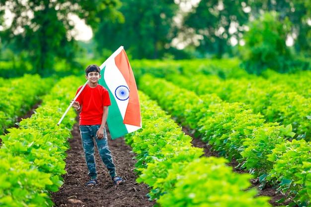 Ragazzino sveglio con la bandiera tricolore nazionale indiana