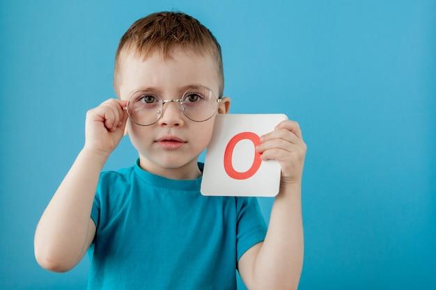 Ragazzino sveglio con la lettera bambino che impara a lettere. alfabeto