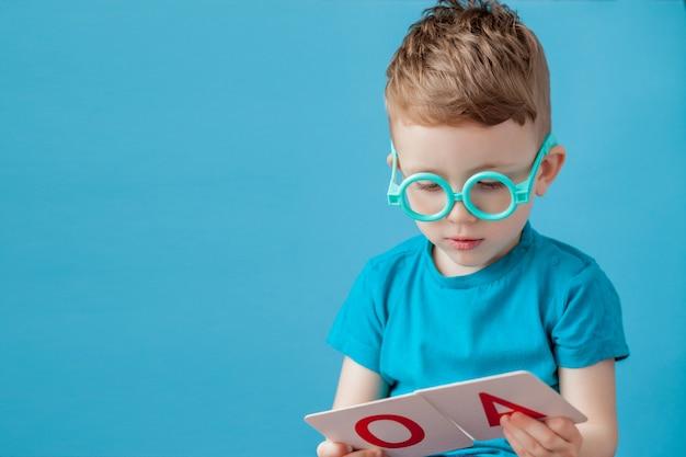 Ragazzino sveglio con la lettera su fondo. il bambino impara le lettere. alfabeto
