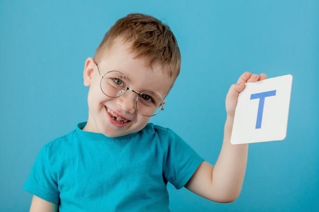Ragazzino sveglio con la lettera sulla parete blu. bambino che impara a lettere. alfabeto