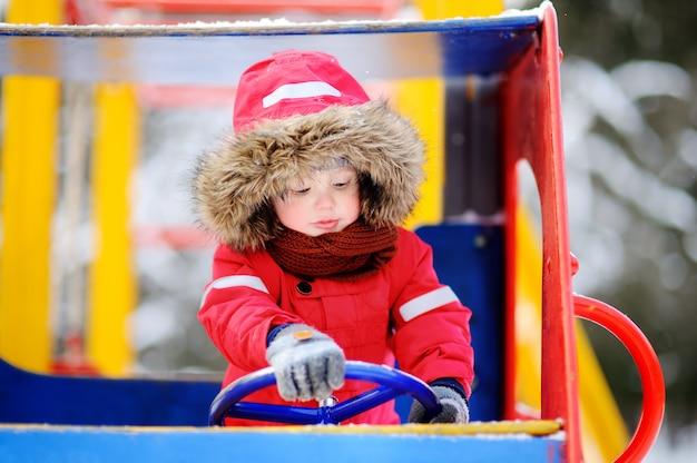 Ragazzino sveglio divertendosi sul campo da giuoco. divertimento invernale all'aperto per bambini piccoli