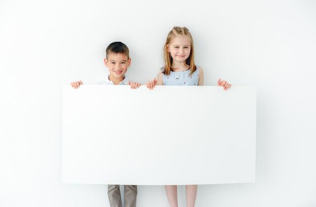 Ragazzino sveglio e ragazza con grande cartello in bianco al chiuso