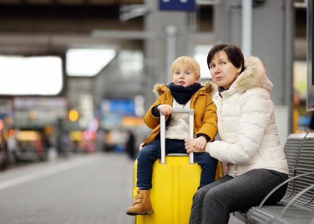 Ragazzino sveglio e sua nonna / madre che aspettano treno espresso sulla piattaforma della stazione ferroviaria