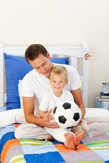 Ragazzino sveglio e suo padre che giocano con un pallone da calcio