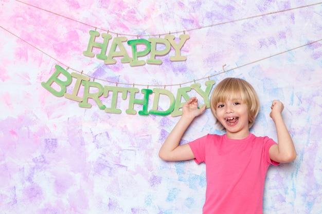 Ragazzino sveglio in maglietta rosa che decora parete variopinta con le parole di buon compleanno