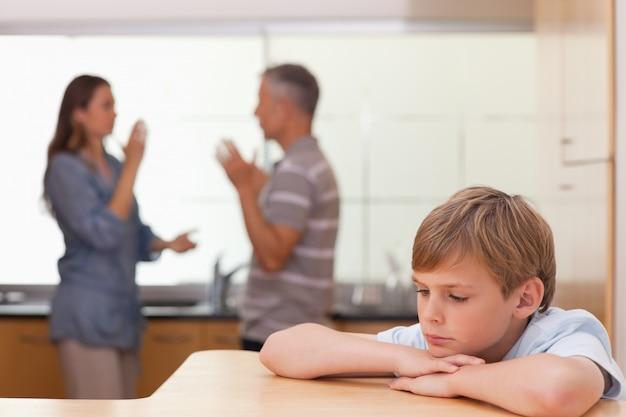 Ragazzino triste che sente i suoi genitori avere discussione