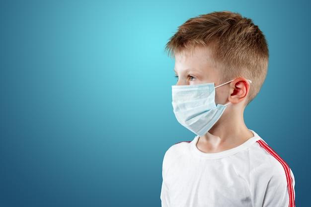 Ragazzino, un bambino in una mascherina medica su un blu