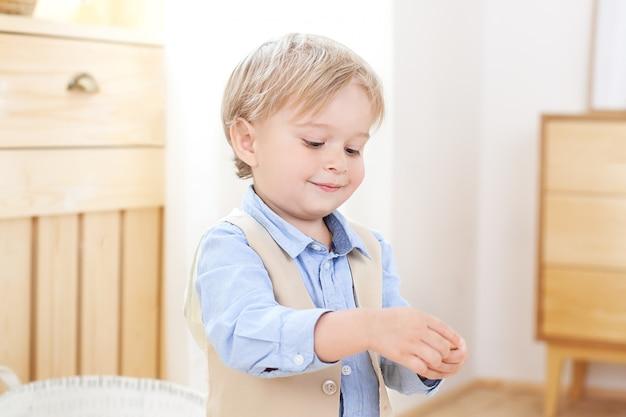 Ragazzino. un ragazzo allegro e sorridente tiene una figura tra le mani. bambino all'asilo. ritratto di bambino maschio alla moda. posa sorridente del ragazzo. concetto di stile e moda per bambini. scandinavo