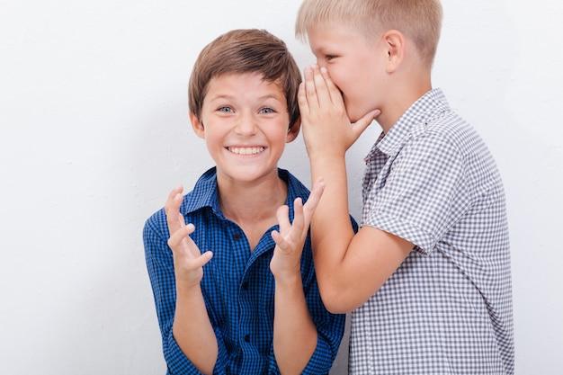 Ragazzo adolescente che bisbiglia un segreto nell'orecchio dell'amico sorpreso su priorità bassa bianca