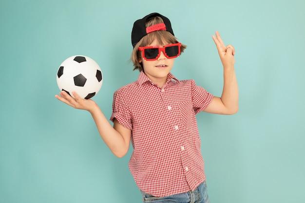 Ragazzo adolescente con cappuccio, occhiali da sole sorride e tiene il pallone da calcio isolato su bianco